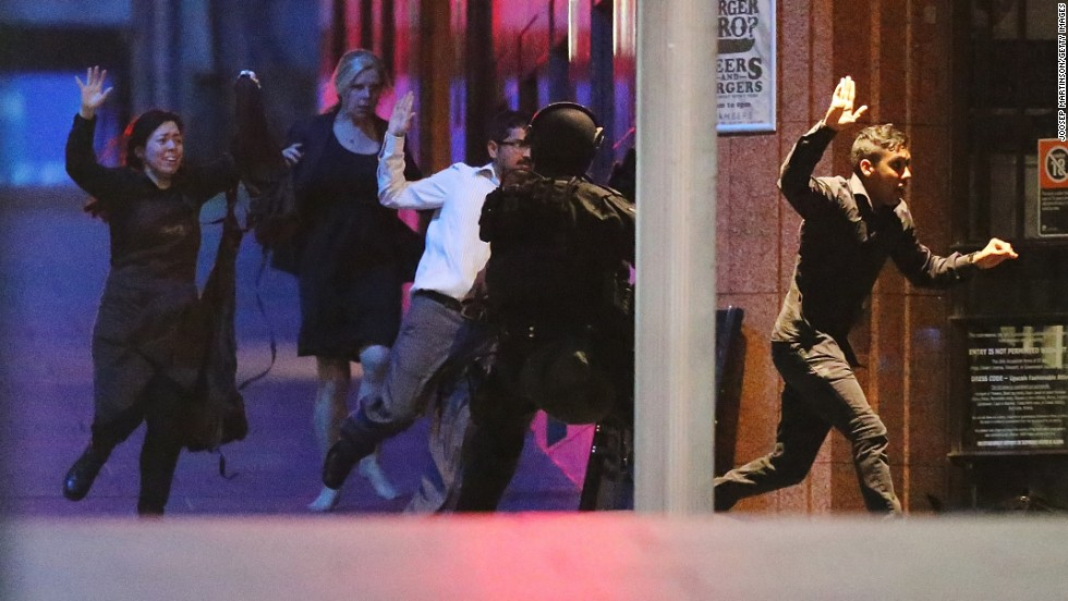 Hostages run toward police officers on December 16.