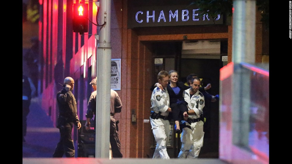 An injured hostage is carried to an ambulance from a cafe in Sydney on December 16. Gunfire erupted early Tuesday as police stormed the Lindt Chocolate Cafe, where a gunman had been holding hostages since Monday morning.