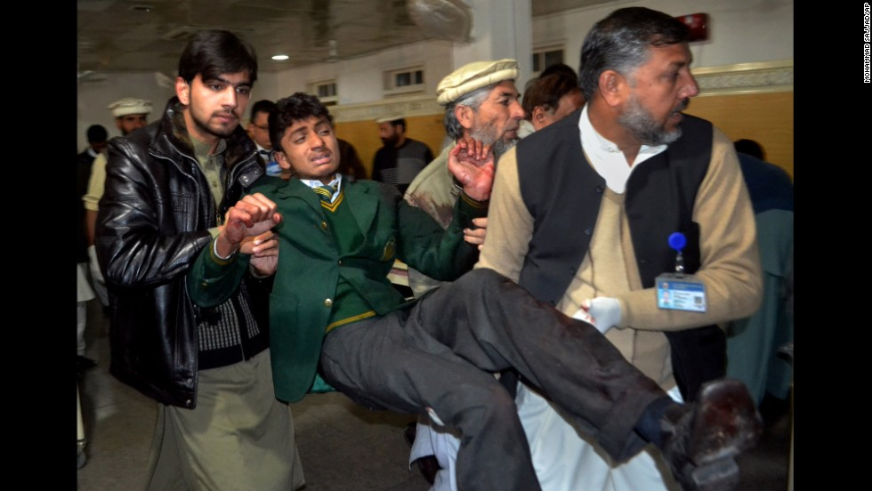 Volunteers carry a student at a hospital in Peshawar.