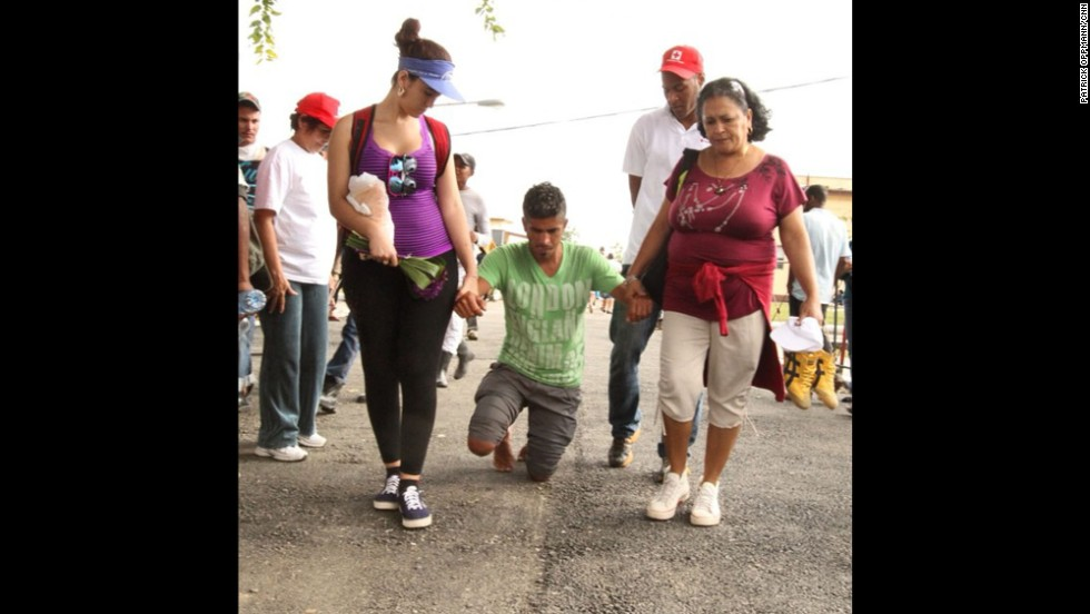 """Cubans celebrate St. Lazarus Day on Wednesday, December 17, by converging on a church known as """"El Rincon"""" outside Havana. """"A deity for followers of both Catholicism and <a href=""""http://www.britannica.com/EBchecked/topic/523208/Santeria"""" target=""""_blank"""">Santeria</a>, St. Lazarus is believed to grant good health to the faithful,"""" Oppmann notes. """"Many believe they need to show their devotion by suffering."""" Here, a man receives help as he walks on his knees to the church."""