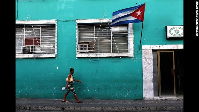A woman walks under a Cuban flag in Santiago de Cuba, Cuba, in March 2012.