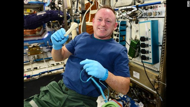 """Astronaut Barry """"Butch"""" Wilmore holds up the ratchet after removing it from the print tray."""
