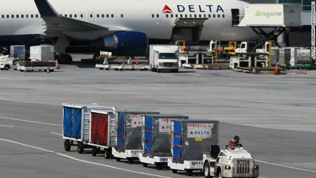 SAN FRANCISCO, CA - JULY 27:  A Delta Airlines baggage cart drives by a Delta Airlines plane at San Francisco International Airport on July 27, 2011 in San Francisco, California.  Delta Airlines reported a 58 percent decline in second quarter earnings with profits of $198 million, or 23 cents a share, compared to $467 million, or 55 cents a share, one year ago.  (Photo by Justin Sullivan/Getty Images)