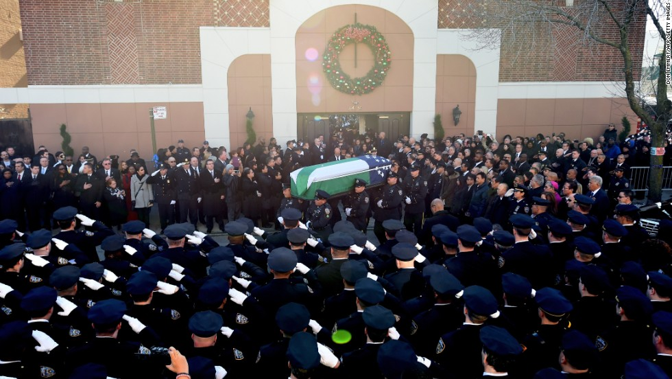 The casket of Officer Ramos is carried out of Christ Tabernacle.