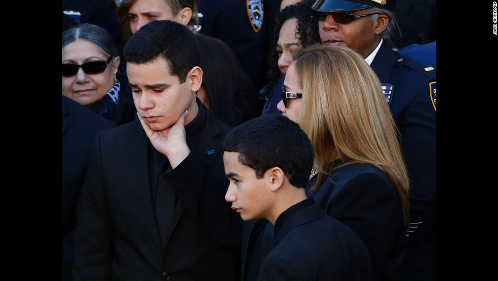 Justin Ramos is comforted by his mother following the funeral service.
