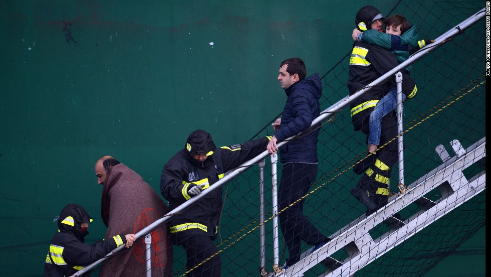 Survivors of the ferry fire are helped by rescuers as they disembark from a rescue ship in the Bari harbor in Italy on December 29.
