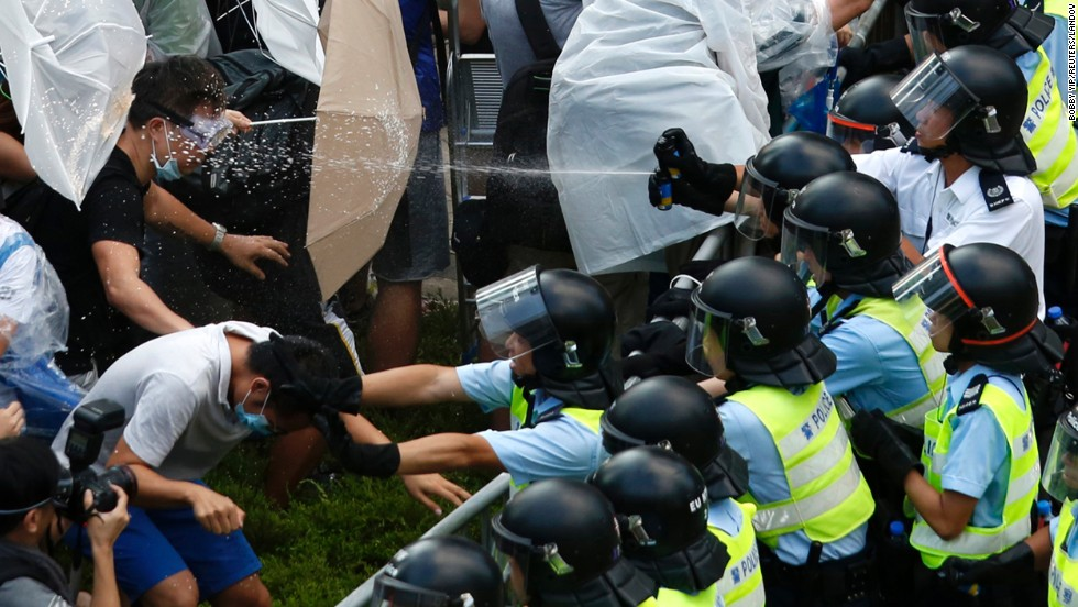 "Riot police use pepper spray as they clash with pro-democracy protesters outside the government headquarters in Hong Kong on September 28, 2014. <a href=""http://www.cnn.com/2014/09/22/asia/gallery/hong-kong-students-protest/index.html"">Demonstrations began</a> in response to China's decision to allow only Beijing-vetted candidates to stand in the city's 2017 election for chief executive. Protesters say Beijing has gone back on its pledge to allow universal suffrage in Hong Kong, which was promised ""a high degree of autonomy"" when it was handed back to China by Britain in 1997. The umbrella has become the defining image of the protest movement, used to shield protesters from tear gas and the elements."