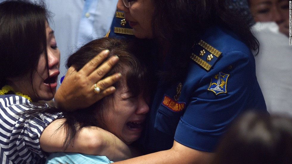 Family members of missing passengers react at an airport in Surabaya after watching news reports on December 30.