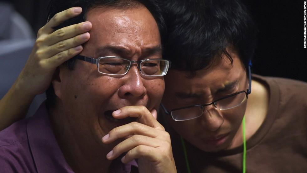 Relatives of missing passengers comfort each other December 30 at Juanda International Airport in Surabaya.
