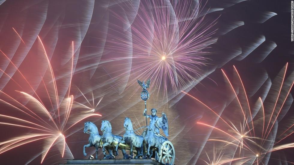 Fireworks explode behind the Brandenburg Gate in Berlin.
