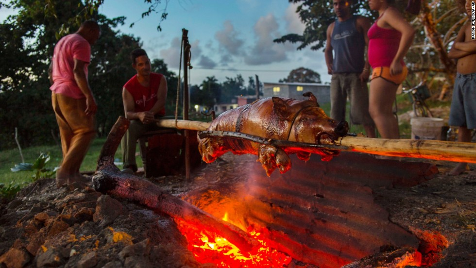 The Rodriguez Osorio family slow-roasts a pig over a charcoal fire for their New Year's Eve dinner in Campo Florido, Cuba.