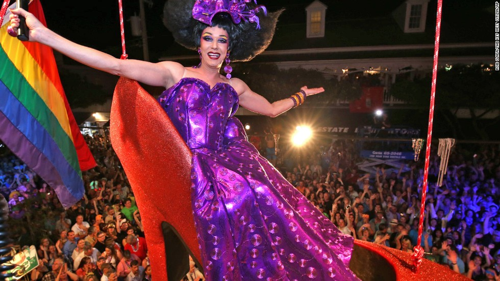 Female impersonator Gary Marion hangs in a giant replica of a woman's high heel over Duval Street in Key West, Florida.
