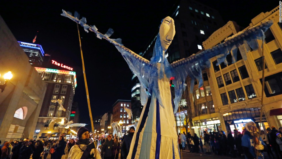 A large puppet is paraded on Boylston Street in Boston.