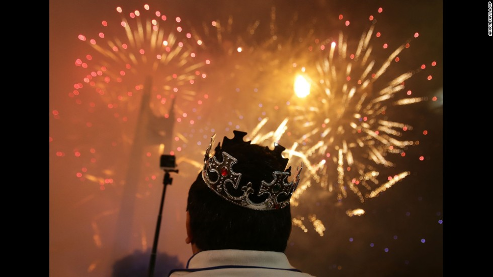 A man watches as fireworks burst over the Manila suburb of Quezon City in the Philippines.