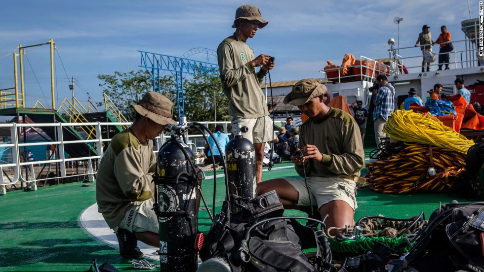 Marine divers prepare their gear on the deck of a ship before searching for passengers and debris January 1 at Kumai port in Pangkalan Bun.