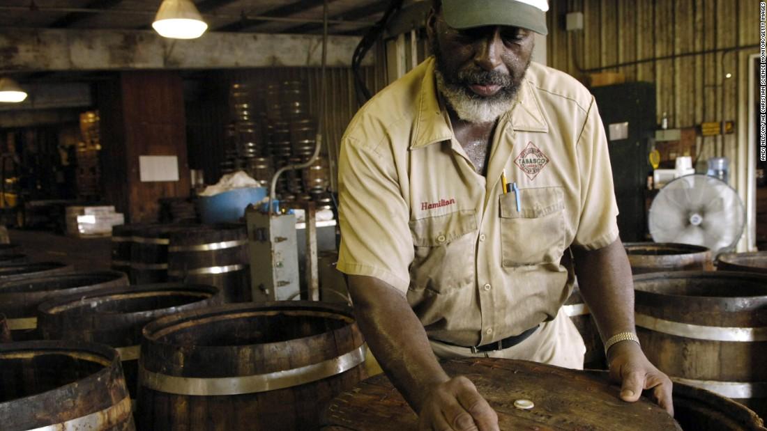 Master barrel cooper Hamilton Polk, now retired, is shown preparing oak barrels for pepper mash.