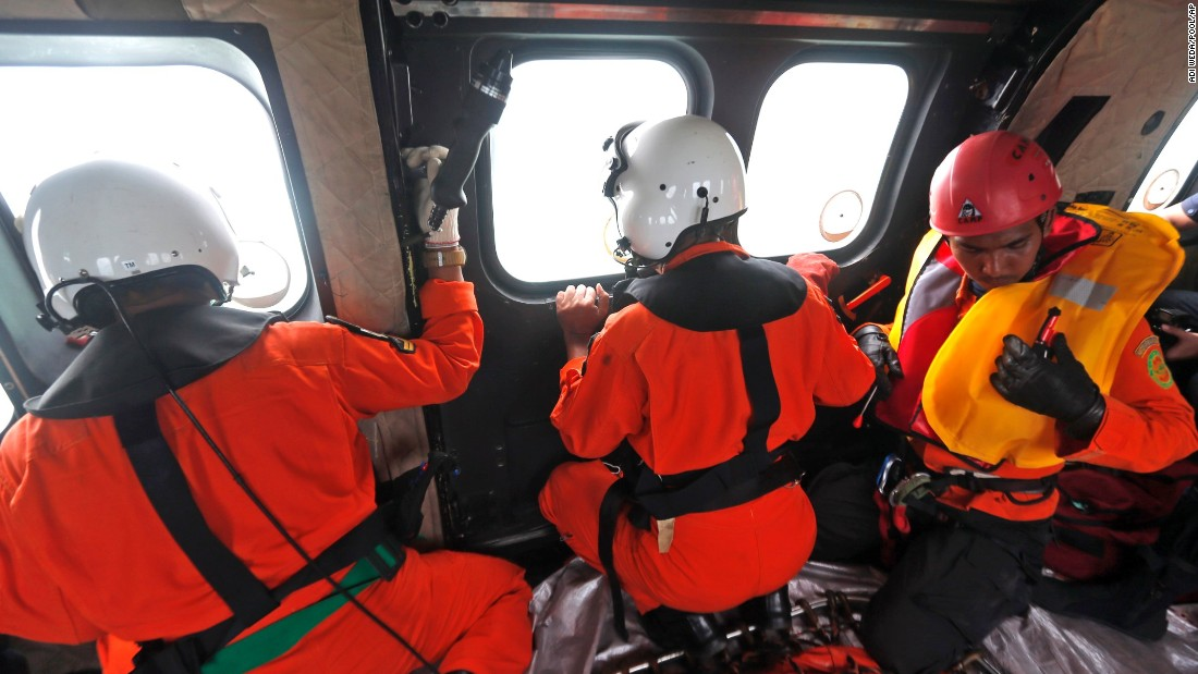 Crew members in an Indonesian air force helicopter look out of the windows over the Java Sea during a search operation on Sunday, January 4.