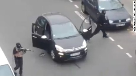 Masked gunmen get out of a car to shoot and kill a police officer in Paris on January 7.