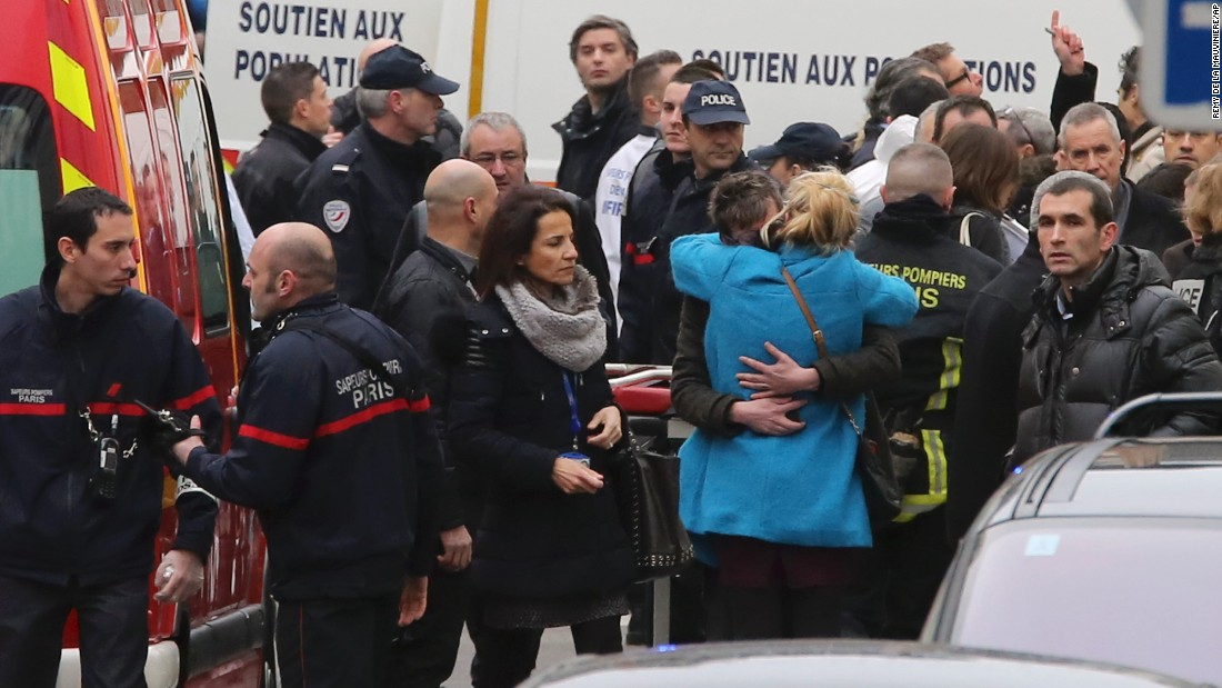 People hug each other outside the magazine's building after the attack.