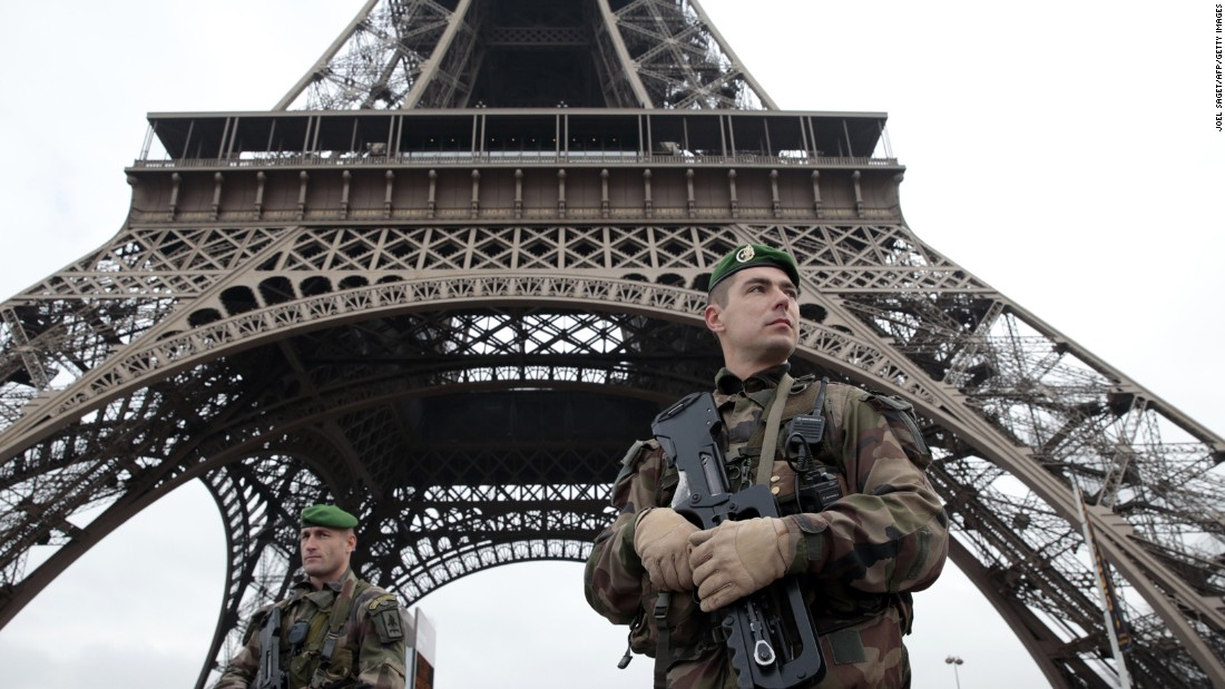 French soldiers patrol around the Eiffel Tower.