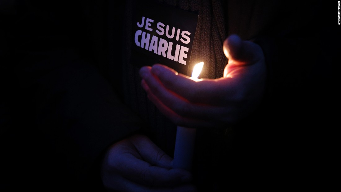 "A man holds a candle and a sticker that translates to ""I am Charlie"" during a vigil in Paris on January 7."