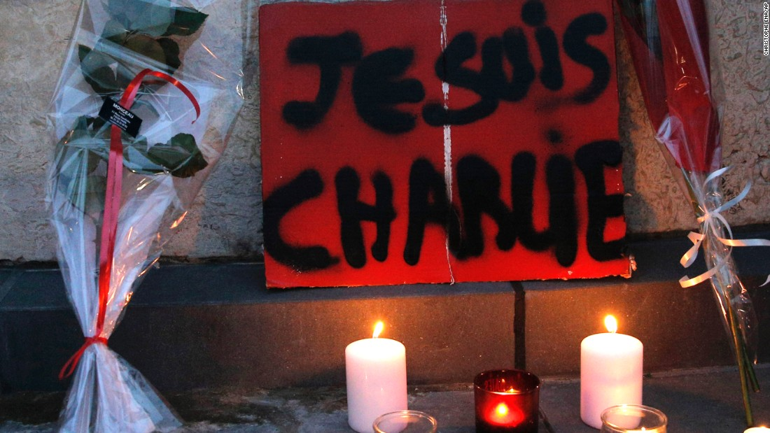 Flowers and candles are placed against a wall during a demonstration in Paris on January 7.