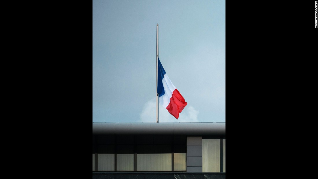 The French national flag flies at half-staff on the roof of the French Embassy in Berlin.