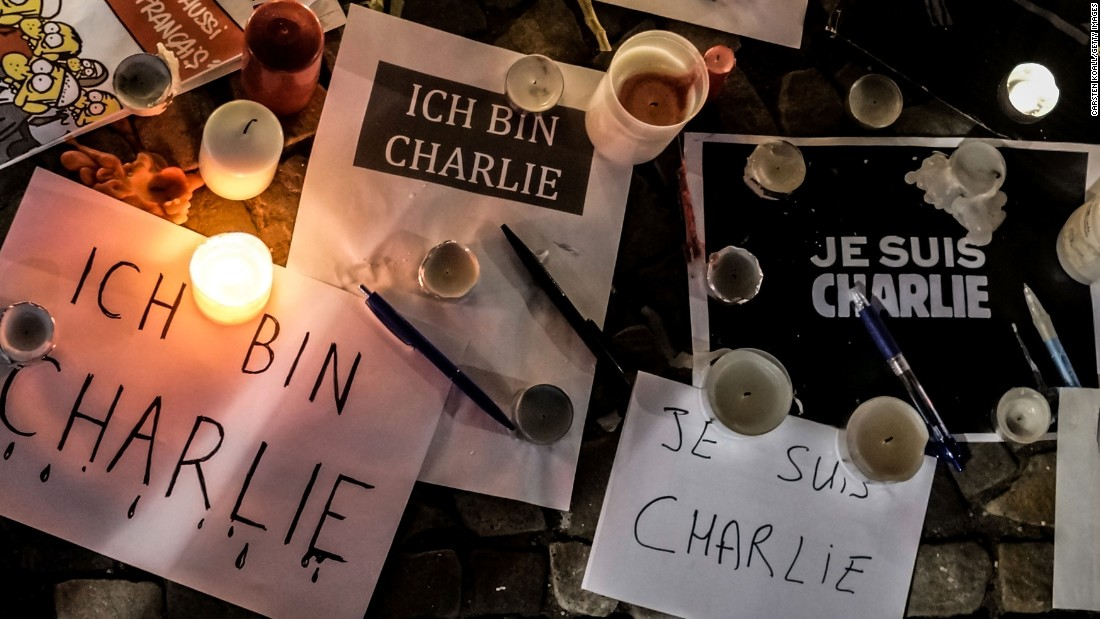 "Papers with ""I am Charlie"" written in various languages are left near candles at a vigil in front of the French Embassy in Berlin."