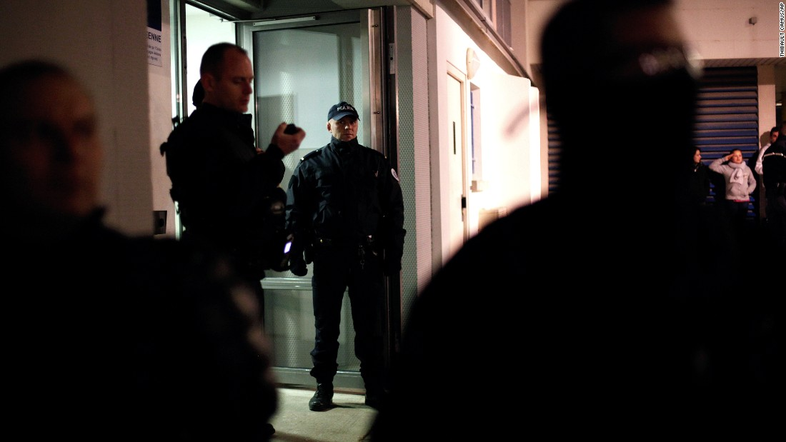 Police stand guard in front of an apartment building in the Croix-Rouge suburb of Reims, France, early on January 8. Forensics officers were looking for evidence related to the three suspects.