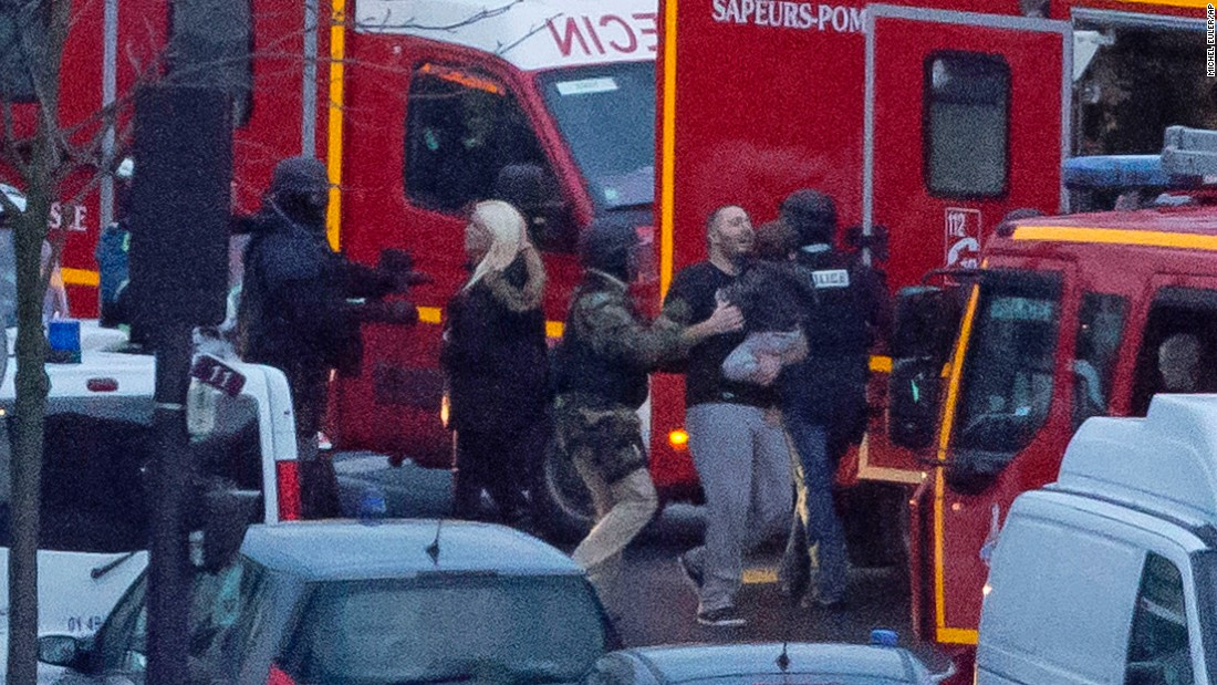 A security officer in Paris directs hostages to safety.