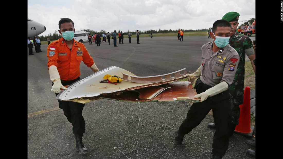 Members of the Indonesian Search and Rescue Agency carry pieces of the jet in Pangkalan Bun on January 9.