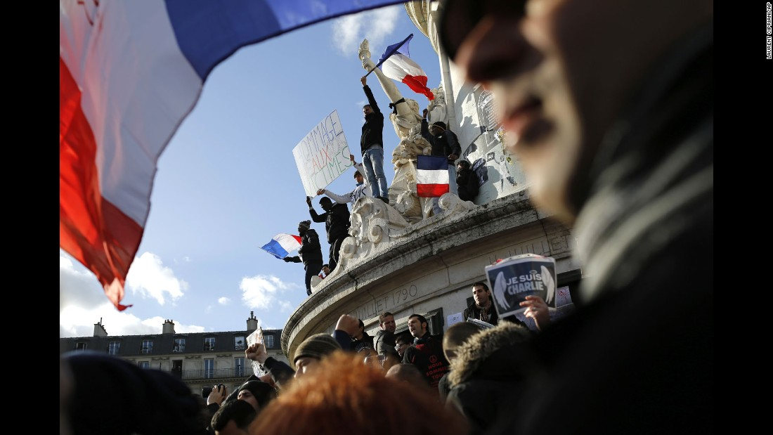 Demonstrators wave flags on the monument at the center of the Place de la Republique before the rally.