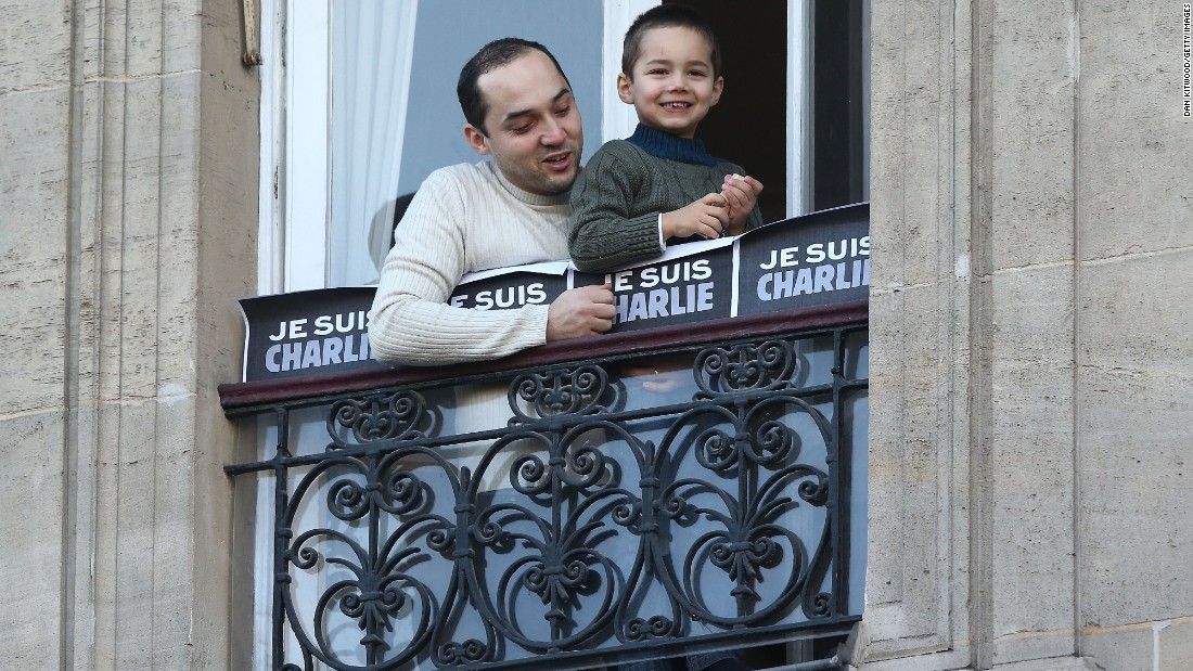 A man and boy watch people gather for the rally from a balcony near the Place de la Republique.
