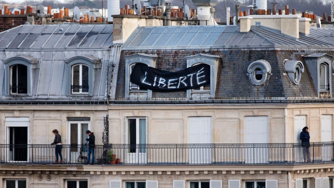 "A banner attached to a house overlooking the Place de la Republique reads ""Freedom"" as thousands of people gather below."