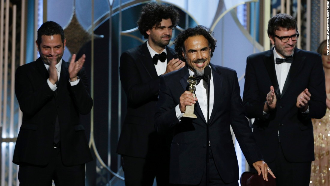 """Alejandro Gonzalez Inarritu accepts the best screenplay award for """"Birdman."""" Michael Keaton, the star of the film, also won a Golden Globe for best actor in a musical or comedy."""