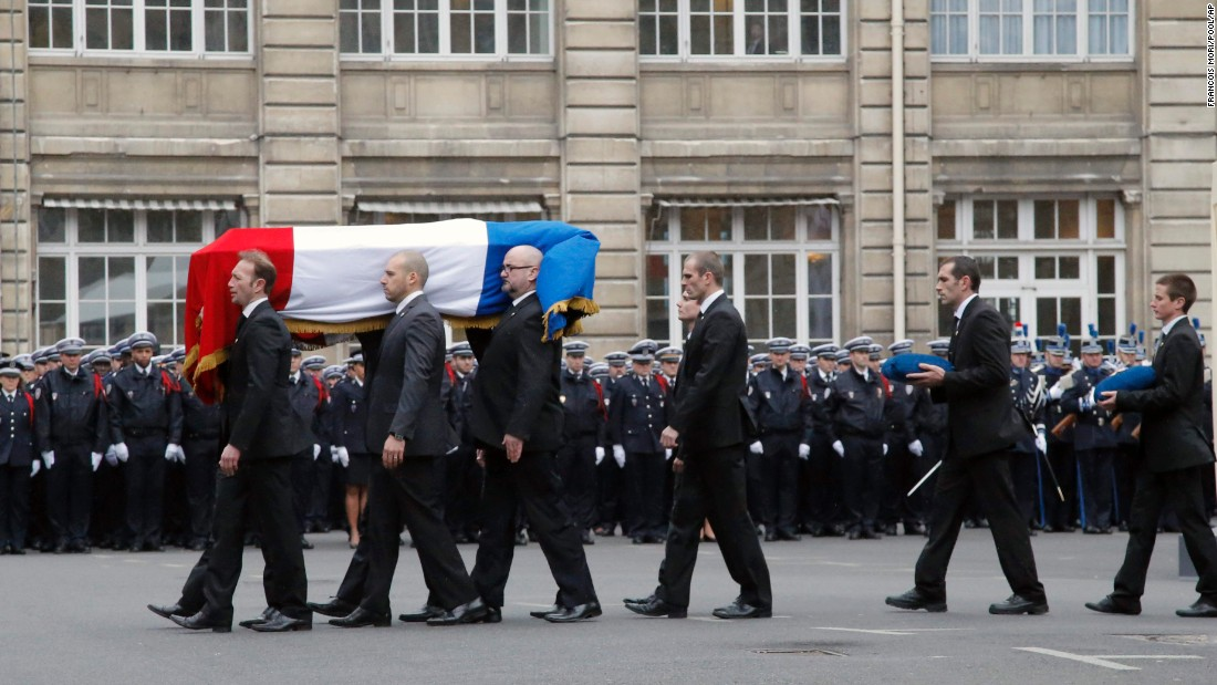 French police officers carry Brinsolaro's coffin. He was a protection officer for Charlie Hebdo's editor, Stephane Charbonnier.