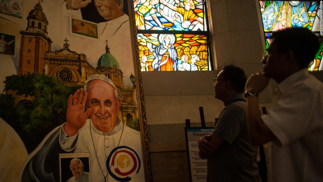 Parish priests look at a montage of paintings of Pope Francis adorning a section of Manila Cathedral on January 7 in Manila, Philippines.