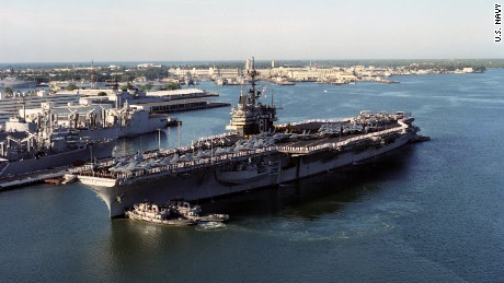 An aerial port side view of Ranger (CV-61), with her Sailors manning the rails and aircraft of Carrier Air Wing 2 (CVW-2) on her deck, as she is nudged into position by harbor tugs Waxahachie (YTB-814), Niantic (YTB-781) and Neodesha (YTB-815), at Naval Station Pearl Harbor, HI, March 8, 1993. US Navy photo by PH3 Bos (DVIC id: DN-SC-05-10867).
