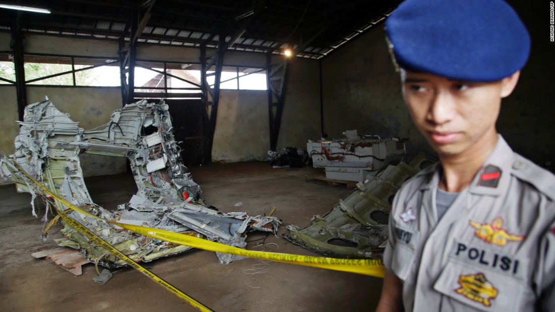 A police officer stands guard near pieces of the plane's wreckage at a warehouse in Pangkalan Bun, Indonesia, on Monday, January 19.