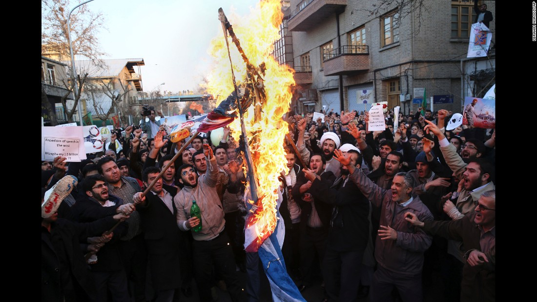 Demonstrators burn representations of Israeli and U.S. flags during a rally against Charlie Hebdo in front of the French Embassy in Tehran, Iran, on January 19.