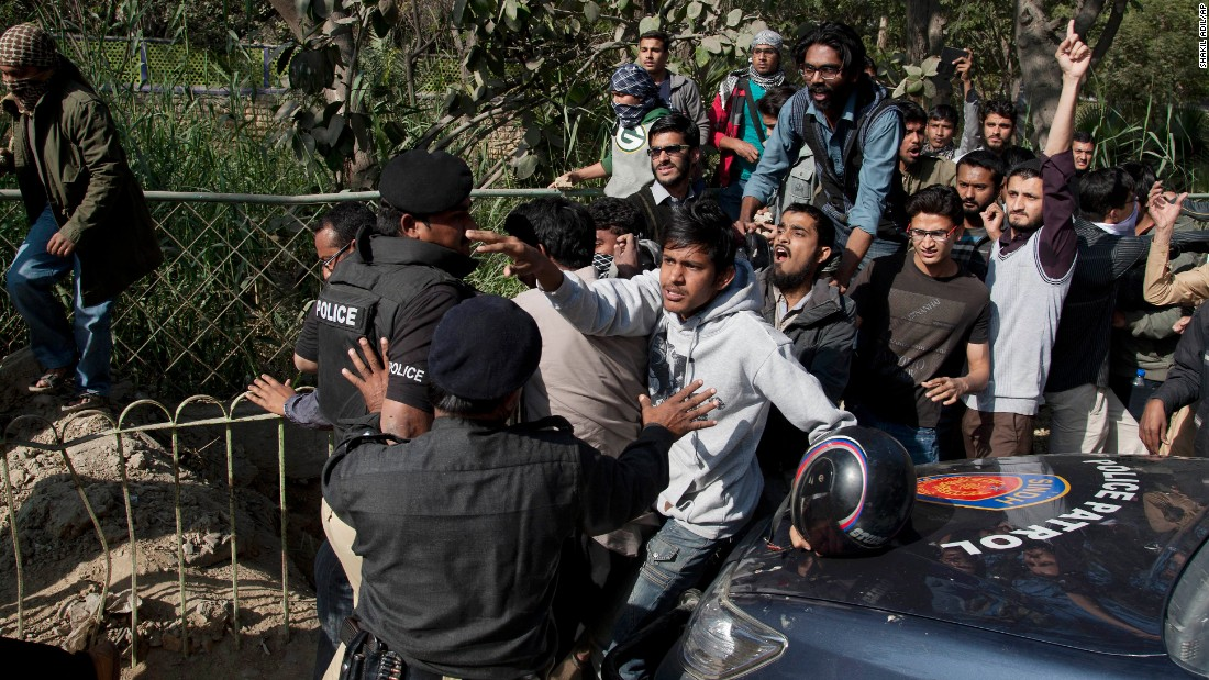 Pakistani police officers block protesters trying to reach the French Consulate in Karachi, Pakistan, on January 16.