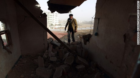 A Yemeni man walks amid the debris inside a heavily damaged house near the presidential palace in Sanaa on Tuesday, January 20.