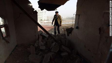 A Yemeni man walks amid the debris inside a heavily damaged house near the presidential palace in Sanaa on Tuesday, January 20.