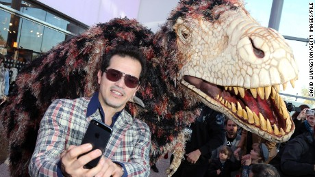 "Actor John Leguizamo shoots a selfie with a dinosaur puppet at the ""Walking with Dinosaurs"" press event at the Natural History Museum on December 12, 2013 in Los Angeles, California.  (Photo by David Livingston/Getty Images)"