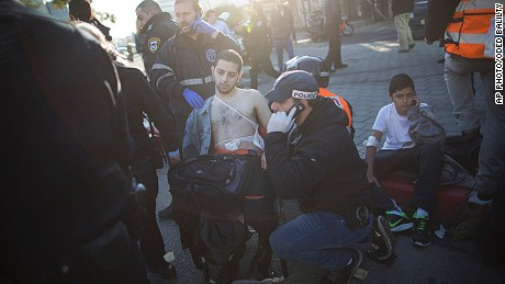 "An Israeli police officer and paramedics treat an injured man at the scene of a stabbing in Tel Aviv, Israel, Wednesday, Jan. 21, 2015. A Palestinian man stabbed nine people, injuring several seriously, on a bus in central Tel Aviv before he was chased down, shot and arrested, Israeli police said Wednesday, describing the assault as a ""terror attack"" in the latest in a spate of violence, the worst Israel has seen in almost a decade. (AP Photo/Oded Balilty)"