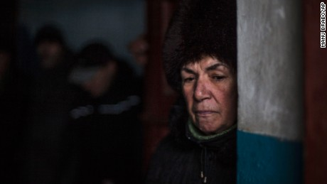 A Ukrainian woman waits for shelling to abate as she shelters inside a building.