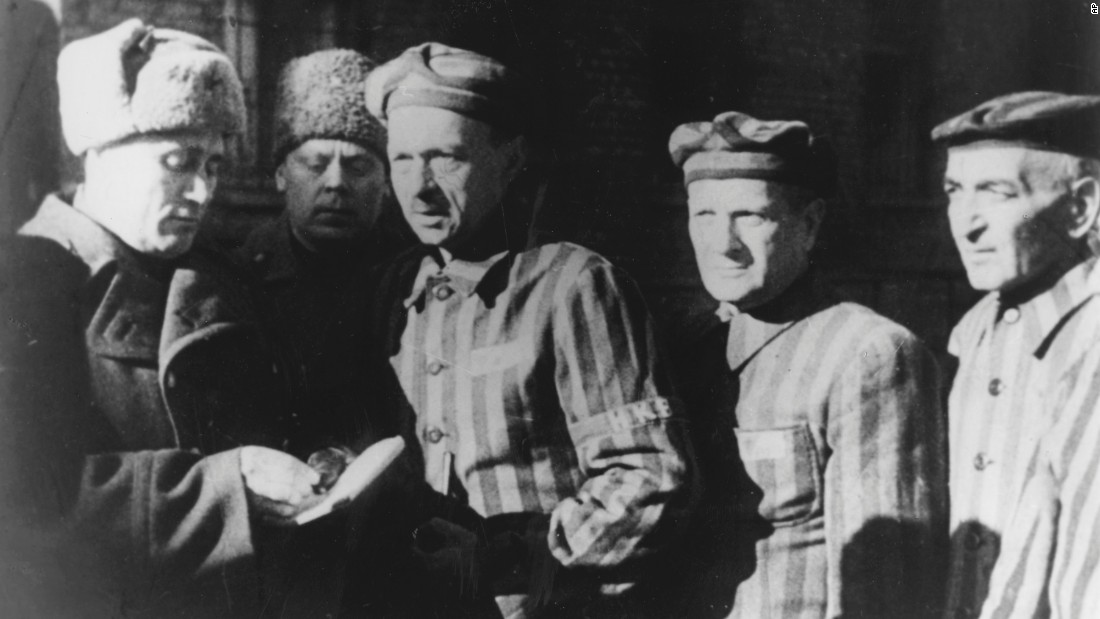 Three prisoners talk with Soviet soldiers who liberated them.