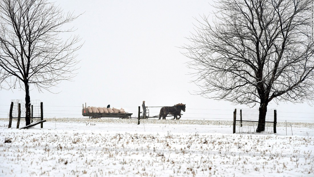 A man hauls farm cargo with a horse-drawn carriage in Leacock Township, Lancaster County, Pennsylvania, Saturday, January 24. Overnight snow brought wet, slushy conditions to the area.