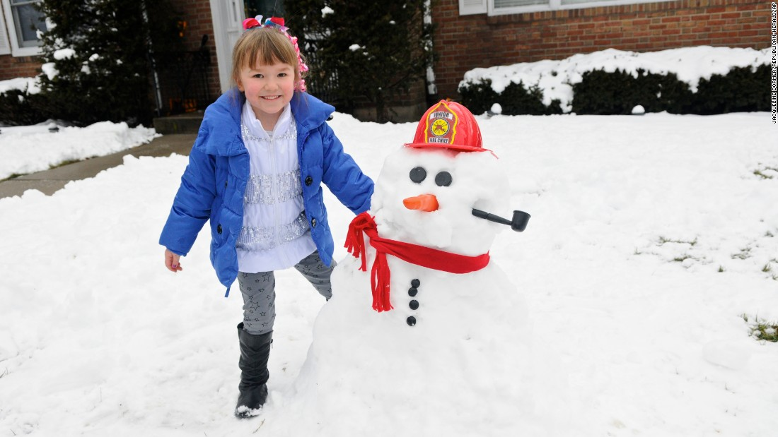 Addison Messner stands next to a snowman Saturday, January 24 in Pottsville, Pennsylvania.