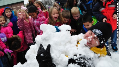 Scotland Elementary School students bury their principal, Tom VanArsdale, in the snow as a reward activity for turning in the most box tops during a schoolwide competition in Scotland, Pennsylvania, on Friday, January 23.